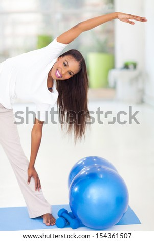 african american woman stretching before exercising - stock photo