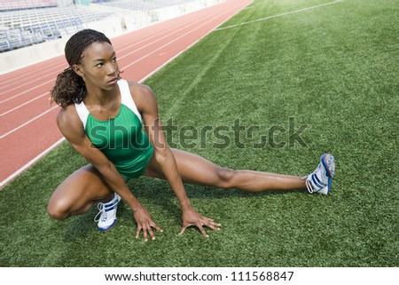 African American woman stretching before race on field - stock photo