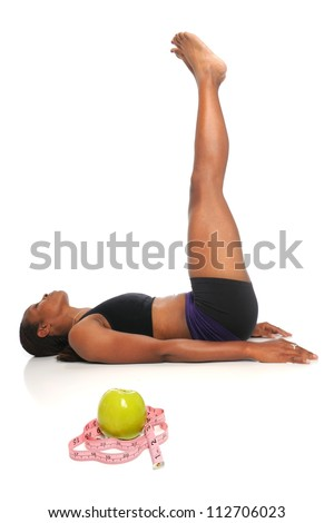 African American woman stretching with apple and measuring tape in foreground - with selective focus on front - stock photo