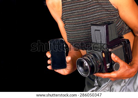 African American woman using both new and old cameras - stock photo