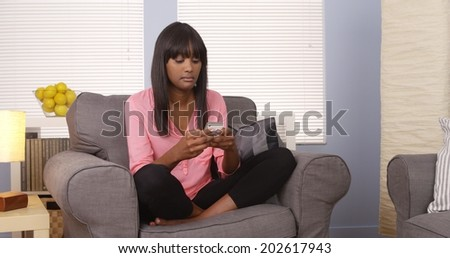 African-American woman using tablet on couch - stock photo