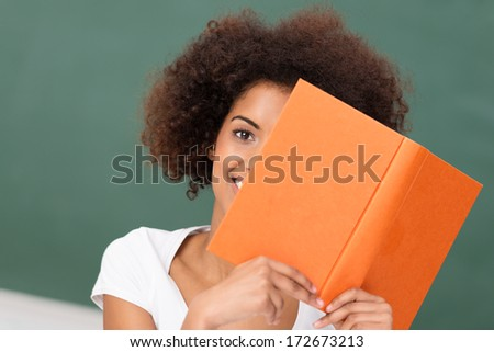 African American woman with a frizzy afro hairstyle reading an orange hardcover book peeping around the edge with one eye at the camera - stock photo