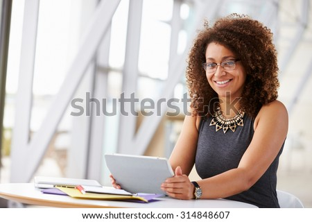 African American woman with tablet, smiling to camera - stock photo
