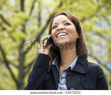 African American young woman talking on mobile phone smiling and laughing. - stock photo
