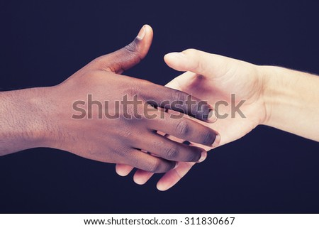 African and a caucasian man shaking hands over dark background - stock photo