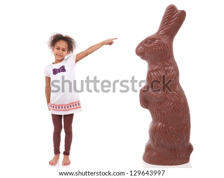 African Asian girl pointing a giant chocolate rabbit, isolated on white background - stock photo