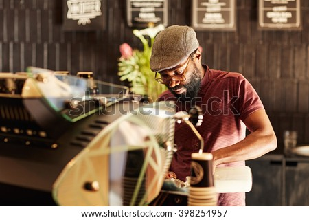 African barista working in a trendy hipster coffee shop - stock photo