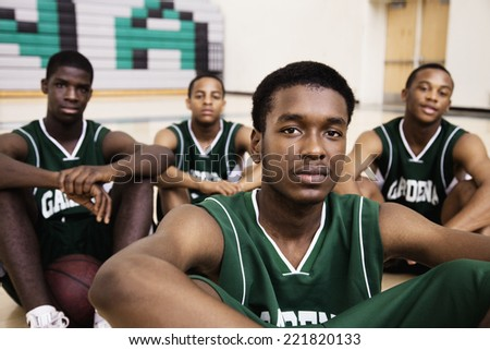African basketball players sitting in gym - stock photo