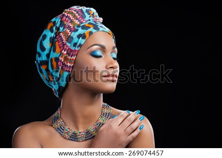 African beauty. Beautiful African woman wearing a headscarf and necklace keeping eyes closed while standing against black background - stock photo