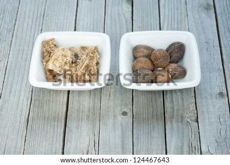 african black soap in square dish and shea butter nuts on old wood table - stock photo