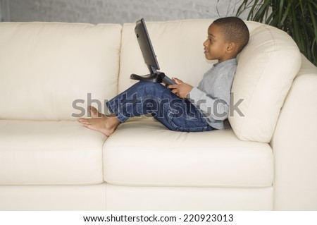 African boy looking at laptop - stock photo