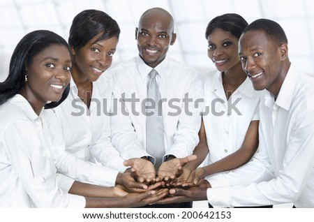 African business team presenting with open hands, Studio Shot - stock photo
