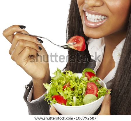 african business woman eating salad and smiling isolated - stock photo