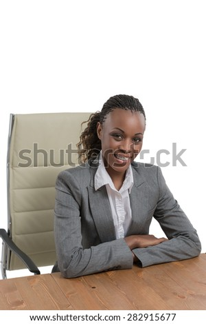 African business woman sitting at her desk and smiling isolated on white background - stock photo