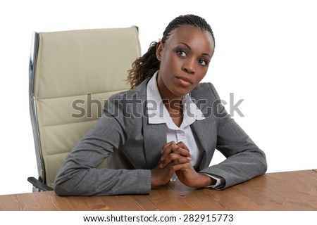 African business woman sitting at her desk and thinking isolated on white background - stock photo