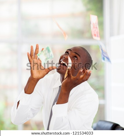 african businessman catching money falling from above - stock photo
