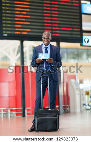 african businessman in airport standing in front of flight information board - stock photo