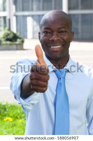 African businessman in front of his office showing thumb - stock photo