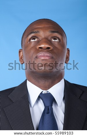 African businessman looking up to the copy space (blue background) - stock photo