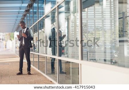 African businessman reading message on his phone outside office - stock photo
