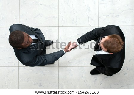 African businessman shaking hands with a caucasian one. view from above - stock photo
