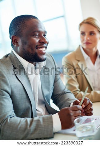 African businessman sitting at workplace in office on background of female colleague - stock photo