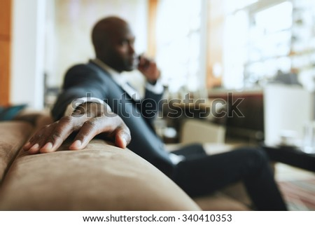 African businessman sitting in lounge area at hotel reception talking on mobile phone, focus on hand. - stock photo