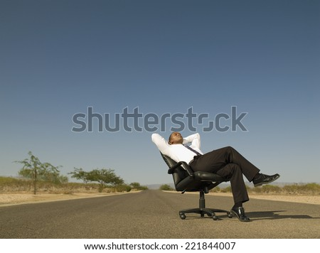 African businessman sitting in middle of road - stock photo