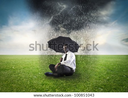 African businessman sitting under an umbrella on a green meadow with stormy cloud over him - stock photo