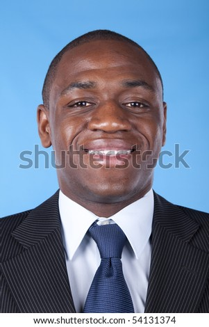 African businessman smiling with a blue background - stock photo
