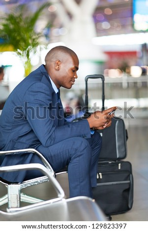 african businessman using cell phone at airport - stock photo