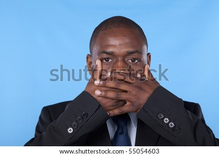 african businessman with hands covering his mouth - stock photo
