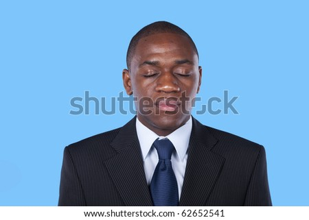 african businessman with his eyes closed (isolated on blue) - stock photo