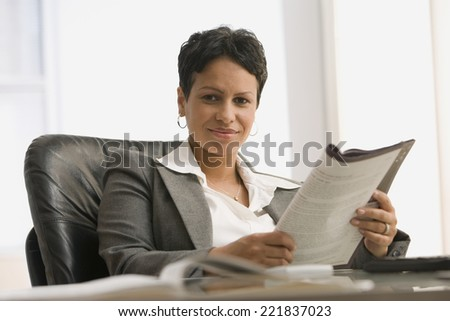 African businesswoman holding paperwork - stock photo
