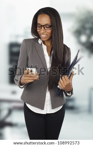 African businesswoman sending text message on mobile phone at office - stock photo