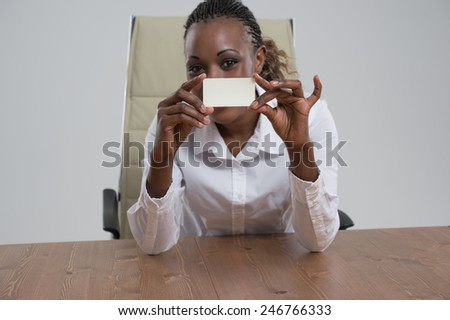 African Businesswoman showing and handing a blank business card. Business woman at workplace at office - stock photo