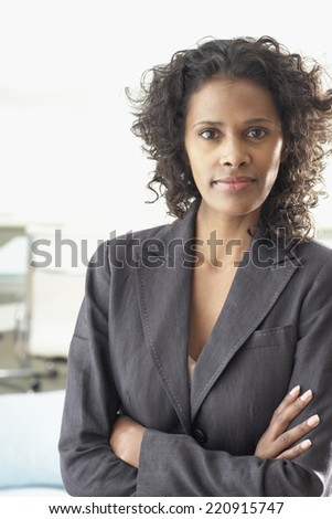 African businesswoman standing with arms crossed - stock photo