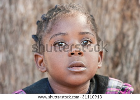 african child with braids having a dreamy face, daydreaming - stock photo