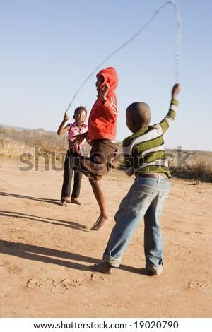 african children jumping rope in the sand, Mmankodi village Botswana - stock photo