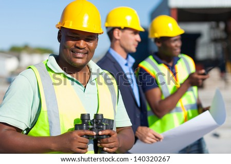 african construction worker holding binoculars standing with colleagues - stock photo