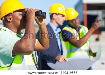 african construction worker using binoculars looking at construction site - stock photo