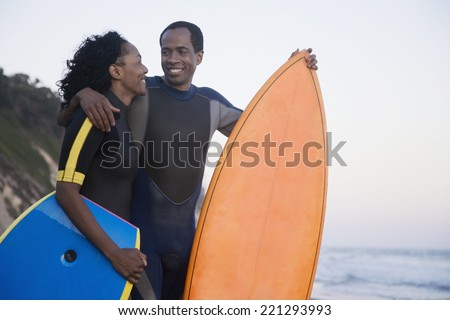 African couple holding surfboard and boogie board - stock photo