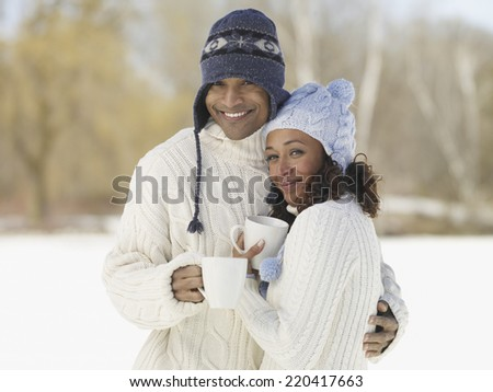 African couple hugging in hats and sweaters - stock photo