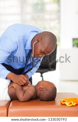 african doctor examining baby boy in his office - stock photo