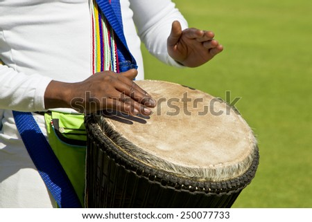 African drummers hands playing a skin covered traditional drum - stock photo