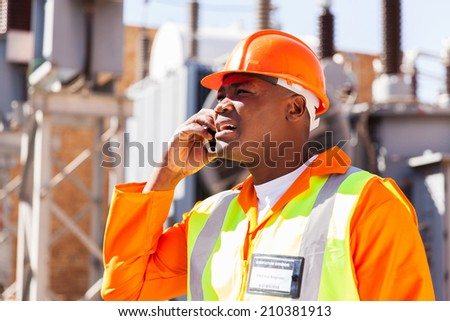 african electrical engineer using cell phone in substation - stock photo
