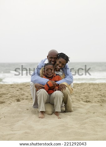 African family sitting on beach - stock photo