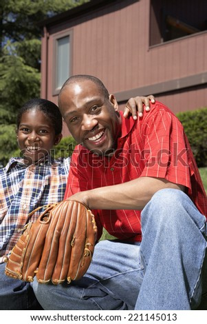 African father and son with baseball glove - stock photo