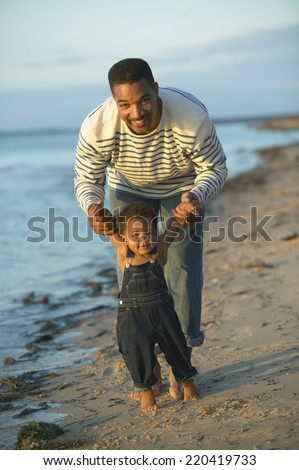 African father helping toddler walk on beach - stock photo