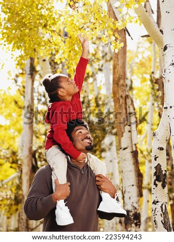 African father holding daughter on shoulders - stock photo